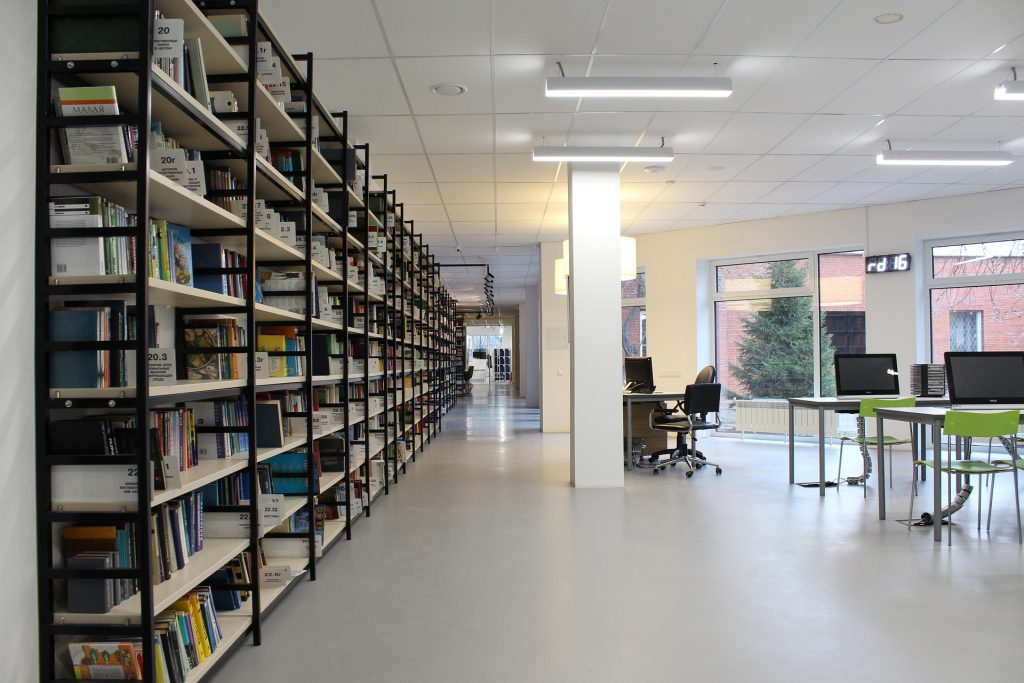 Image of a public library showing bays of shelves and computers